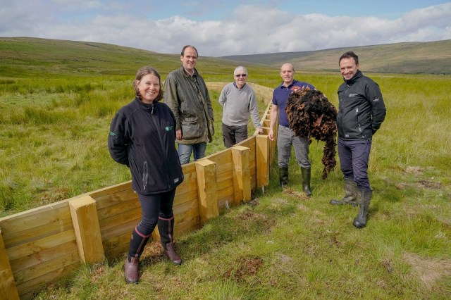 The image shows members of the Environment Agency, construction team and the local MP at the site of one of the features.