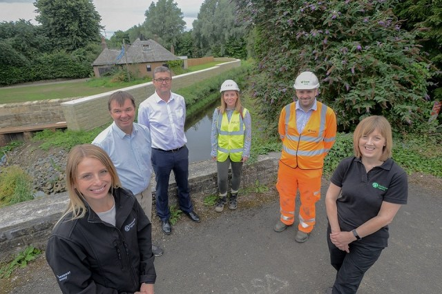The image shows representatives from the Environment Agency, designers Arup, and construction company BAM Nuttall with MP Guy Opperman.