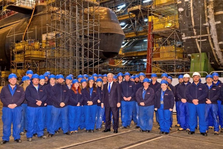 Defence Secretary Sir Michael Fallon with BAE Systems apprentices inside Devonshire Dock Hall where HMS Agamemnon is under construction.