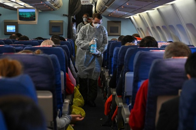 FLIGHT. A crew member of a French evacuation flight from Wuhan hands disinfectant to passengers during the flight to France on February 1, 2020. Photo Hector Retamal / AFP