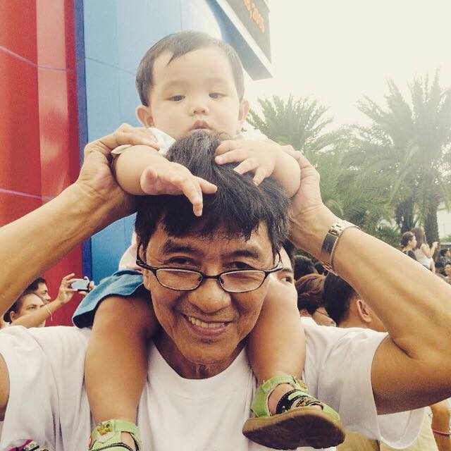A grandfather carries his grandson who is barely a year old, while waiting for Pope Francis in MOA