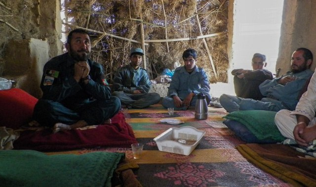 In this photograph taken on April 28, 2016, Afghan police commander Seddiqullah, 30, (L) sits alongside his subordinates as he speaks during an interview at a checkpoint in Tarin Kot, capital of southern Uruzgan province. Seddiqullah voiced concern about Taliban insider attacks carried out by child sex slaves. Photo by Rateb Noori/ AFP