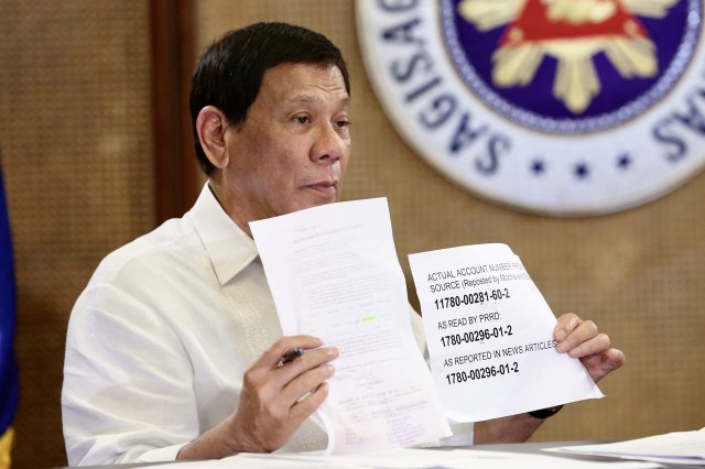 'TRAP' FOR TRILLANES. President Rodrigo Duterte holds up a paper comparing the 'actual' bank account number of Senator Antonio Trillanes IV and the bank account number he 'invented.' Malacañang photo