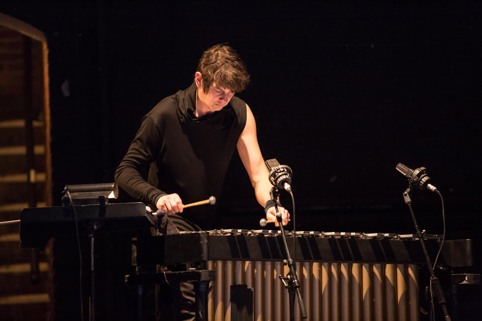 Drummer Glenn Kotche playing music on a dark stage