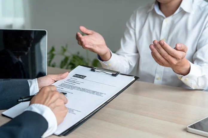 भर्ती प्रबंधक एक साक्षात्कार के दौरान नौकरी के उम्मीदवार का बायोडाटा पढ़ता है