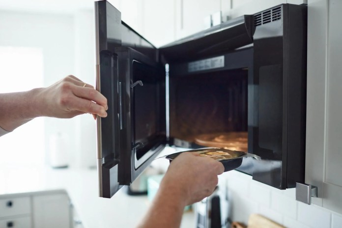 male putting food into a microwave