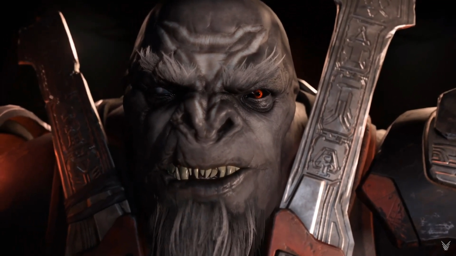 Escharum, a large aggressive alien who resembles a gorilla, looks intently into the camera in close up. He has a long grey chinbeard, and red eyes.