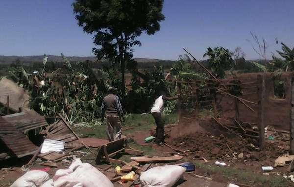 Stephen Munyereri (a sinistra) con il figlio, tra le macerie della sua casa. La foto è stata scattata pochi minuti prima che Munyereri venisse ucciso.
