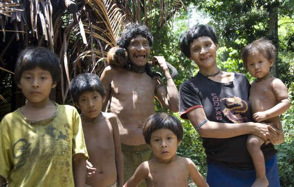 Familia awá. Las mujeres awás a menudo cuidan de crías de monos dándoles de mamar.