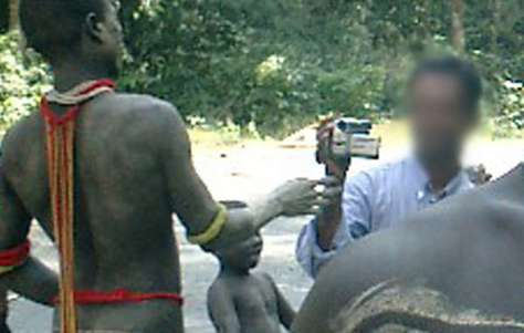 A tourist films a Jarawa man up close on the road. Campaigners have raised deep concerns about the dangerous, degrading and exploitative nature of tribal tourism.