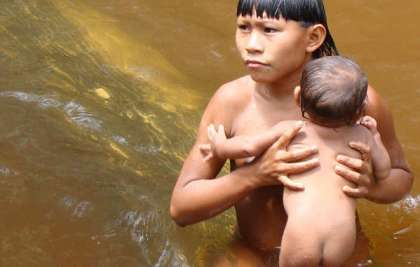 A Suruwaha boy bathes a young baby in a stream.
