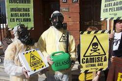 Manifestantes en Londres con máscaras de gas y carteles denuncian las consecuencias letales del proyecto Camisea para los indígenas aislados de Perú.