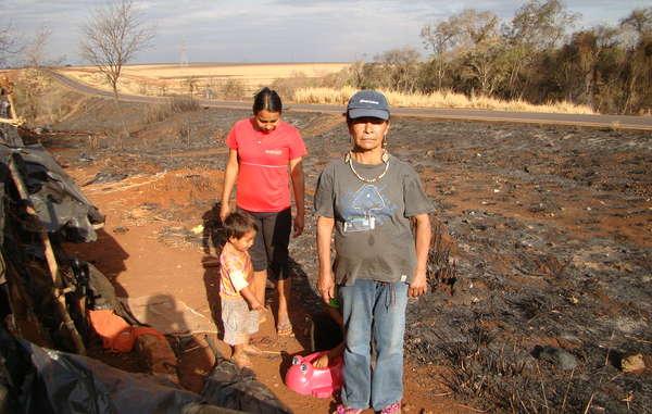 Damiana, leader della comunità di Apy Ka'y, tra i resti dell'accampamento distrutto da un incendio.