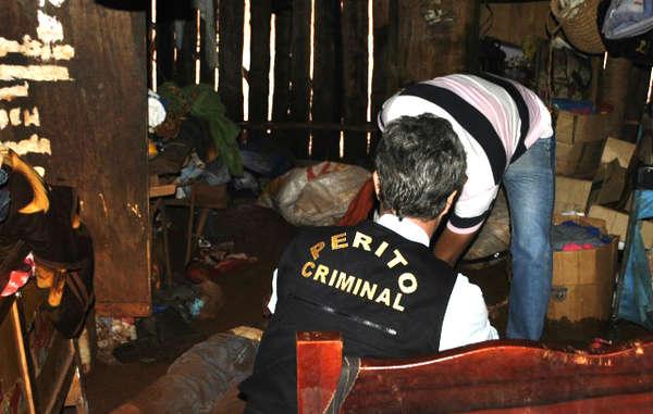 Les policiers examinent le corps d'Ambrósio à l'intérieur de sa maison.