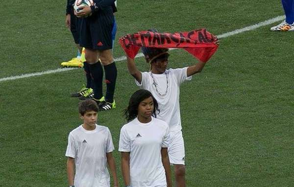 An indigenous Guarani boy held up a banner reading 'Demarcation Now!' at the World Cup's opening ceremony.