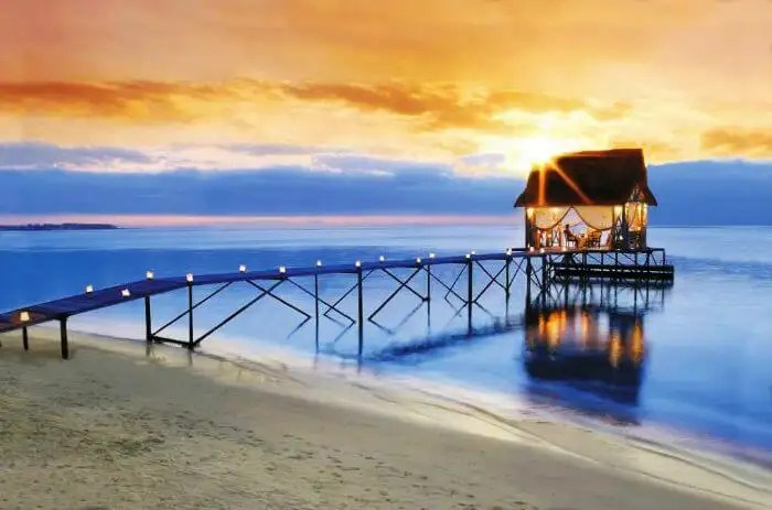 A candlelit pathway leading to an overwater shack, set for a romantic evening at Trou Aux Biches in Mauritius
