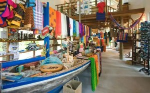 Colourful clothes on a wooden boat in a shop