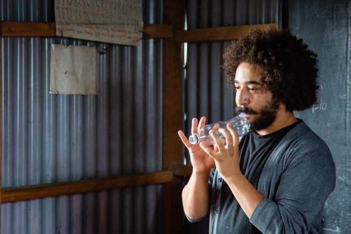 Shady Rabab con una flauta hecha de una vieja botella de plástico.  Foto del PNUMA