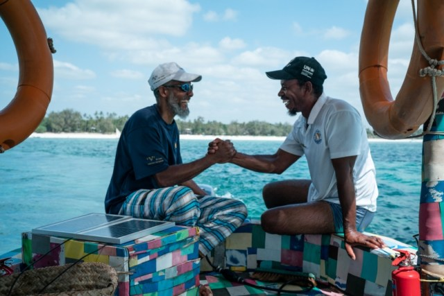 Two men shaking hands on boat