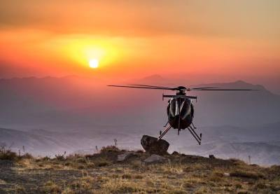 Helicopter in foreground as sun warms a mountain range.