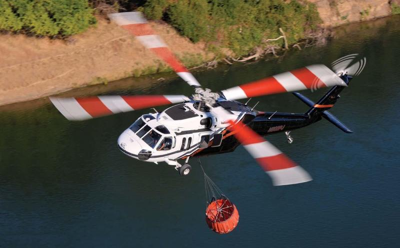 A PJ Helicopters Sikorsky UH-60 Black Hawk prepares to collect water during a firefighting operation. The company is one of several to take advantage of the recent availability of Black Hawks in the civilian marketplace.