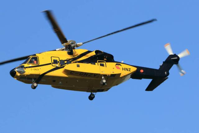 A yellow helicopter flies through the air.