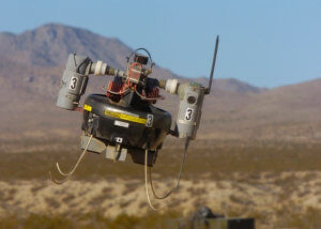 A micro air vehicle flies over a simulated combat area during an operational test flight. The MAV is in the operational test phase with military Explosive Ordnance Disposal teams to evaluate its short-range reconnaissance capabilities. 3W Photo