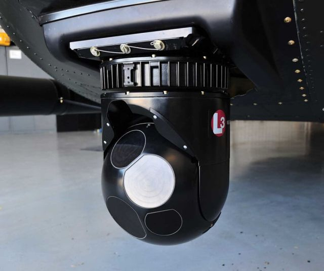 An inactive Wescam Matrix weapon system hangs under the aircraft's nose.