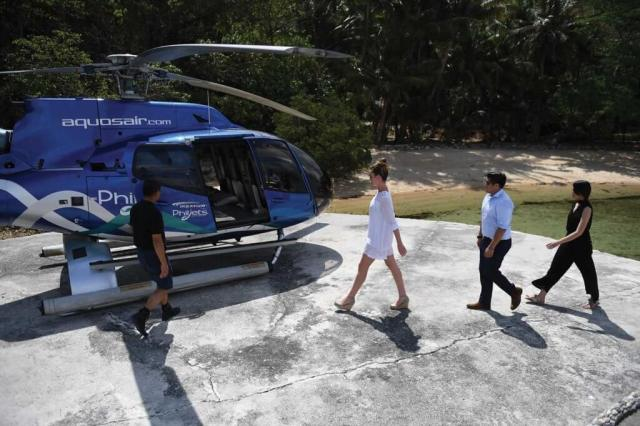 Three people walk behind one another on a helipad, toward a waiting PhilJets helicopter.