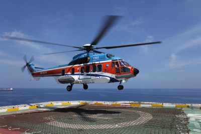 A VNH South Airbus H225 helicopter hovers over a helipad.