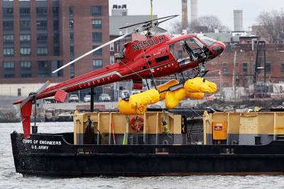 A Liberty Helicopters Airbus AS350 B2 is hoisted out of the East River on March 12. AP Photo/Mark Lennihan