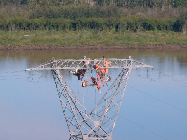 Powerline technicians attach the SkyWrap to the powerline to take the fiber optic cable across the Peace River. Slave Lake Helicopters Photo