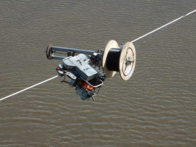 The SkyWrap cable works its way along the powerline. Slave Lake Helicopters Photo