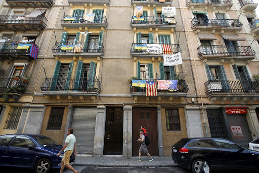 Banners against tourist apartments hang from balconies in Barcelona.