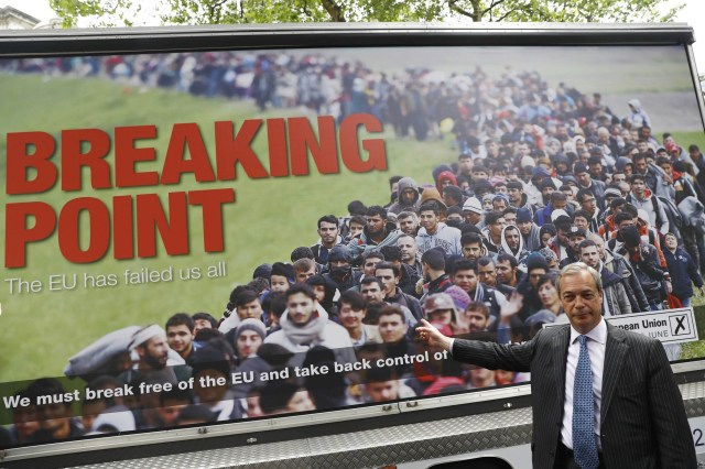 Nigel Farage, the former UKIP leader, stands in front of a poster used by pro-Brexit campaigners.