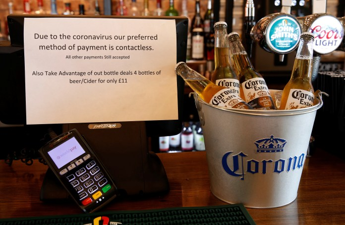 A sign asking customers to only use contactless payment methods is seen in a pub in Liverpool, Britain March 17, 2020. REUTERS/Phil Noble - RC2QLF92NYGX