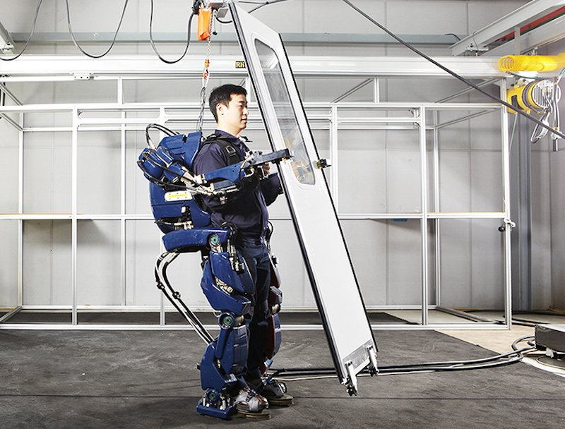 Man wearing Hyundai exoskeleton and lifting door
