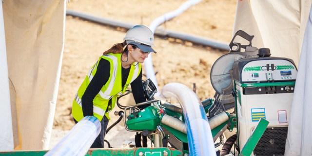 Une femme conduit une machine de soudage pour tubes en plastique