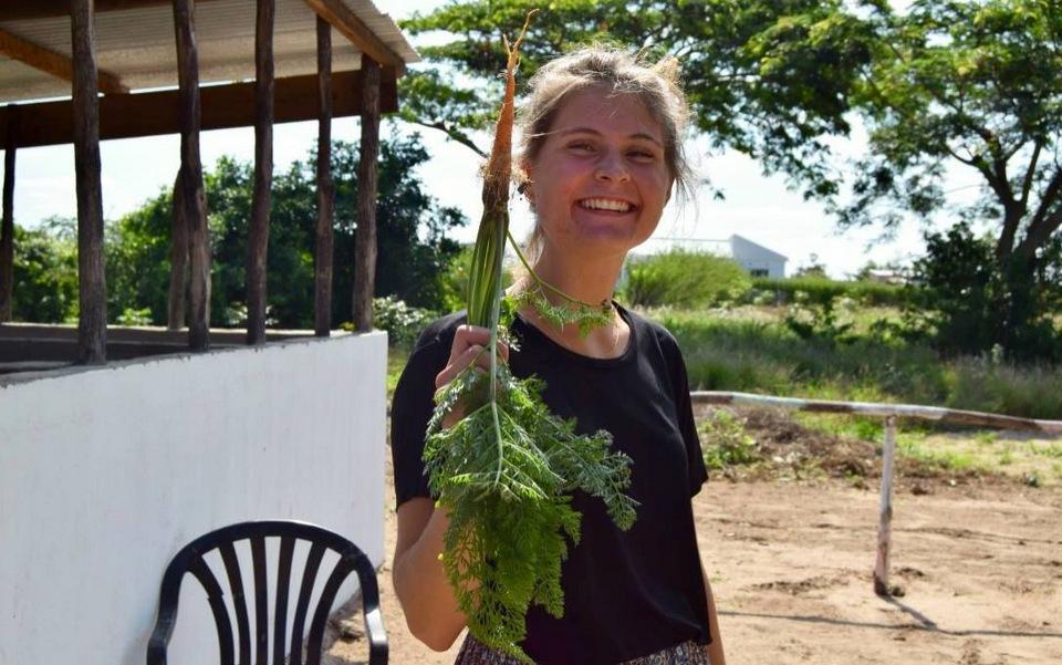 Cecilie med en nyopgravet gulerod fra machambaen. Mums