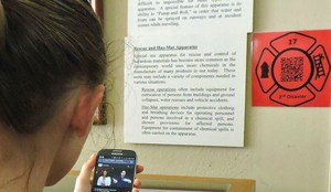 a person scanning a qr code displayed on the wall with their phone to watch the exhibit's ASL video tour