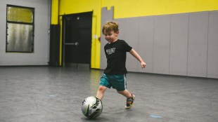 a little boy kicking a soccer ball at the oak city soccer venue