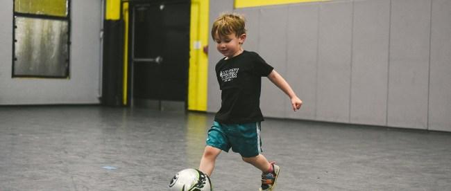 a little boy kicking a soccer ball at the oak city soccer venue