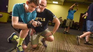 A staff member showing a student how to operate a camera.