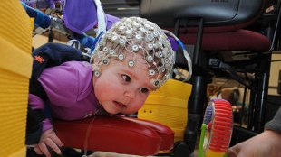 An infant shown wearing an electrodes studded cap. A second person is holding a toy in front of her, to encourage her to move towards the toy.