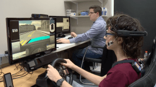 An adolescent hooked up to sensors and driving the virtual reality simulator