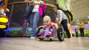 Evelyn seen wheeling around in a public place in her DIY wheelchair that her parents built her.