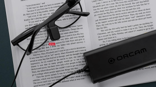 a pair of glasses with orcam myeye attached to the right stem resting on a book