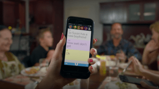 A person shown holding their phone at the dinner table. The phone shows Ava showing all the dialogues of people at the dinner table.