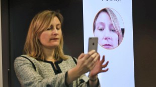 a person taking a selfie on her phone to make a payment