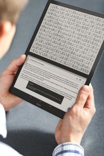 A person is holding a blitab in his hands. There is text displayed in the bottom screen, and the braille equivalent of it is displayed on the top screen.